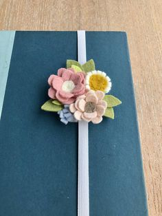 This sweet bookmark would make a great gift for that special someone (including yourself). Perfect for journal writing, reading or keeping those pages in place during your summer reading. Handcut felt flowers are securely fastened to base of bookmark and a handsewn blanket stitch