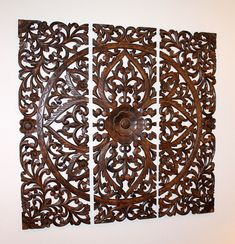 Hand carved teak wall decor. I have this hanging above my sofa. Not very easy to hang since it comes in three sections but my husband was able to get it done with no gaps between the panels and it looks fabulous.