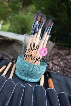 This beautiful glitter dipped make-up brush holder is the perfect addition to your vanity to add some shimmer and sparkle. Get ready (and organized!) in style!  Glass is HIGH QUALITY and very sturdy. Glitter comes in any color under the rainbow. It is permanently sealed so it wont flake off on your hands.  Lettering is all-weather vinyl (same vinyl used for car decals), and comes in over 40 colors. Default saying is hello gorgeous with lips, but this can be personalized to say anything…