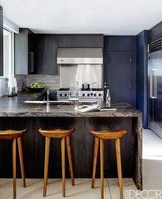 Minimalist kitchen design with black cabinets and extra-ordinary bar chairs