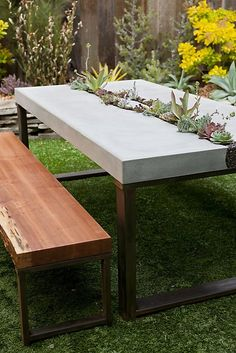 Concrete succulent table. Five Feet from the Moon's elegant table features a living centerpiece and redwood benches made from a fallen tree. $6,000, including plants, $8,000 with redwood benches. www.fivefeetfromthemoon.com