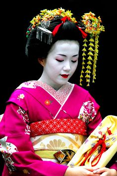 an advanced maiko. she'll soon be a fully fledged geisha. you can tell by her hair-do and collar
