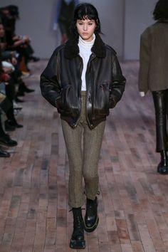 black boots black leather jacket white turtleneck green khaki pants