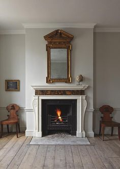 Fisher always aims to capture the essence of the classical English country house. A pair of oak hall chairs stand on the side of an antique chimney piece that inspired Jamb's Oxford stone chimney piece. Above the chimney piece is a George II giltwood mirror
