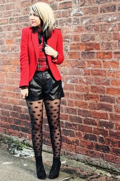 Black pantyhose with opaque circles, black leather shorts and red jacket over tartan shirt