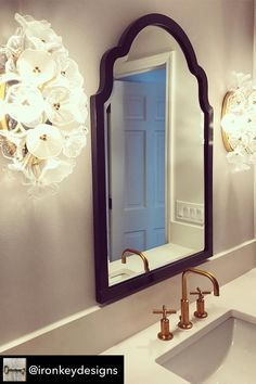 The Sultan Mirror, shown here in a bathroom designed by Iron Key Designs, is a gorgeous piece. The wood frame is shaped like a fancy archway. It is then finished in our glossy black lacquer. The mirror on this piece is beveled adding to its style and beauty. The Sultan Mirror is part of our custom paint program and is available in one of fourteen vivid colors. It is proudly painted in the USA.  #bathroommirror #fancymirror #blackmirror #howardelliottmirror