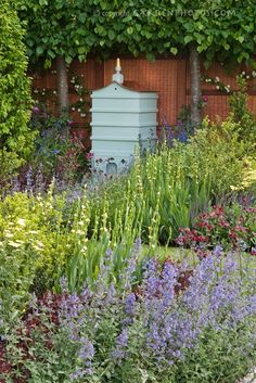 Beehive in beautiful spring garden with bee friendly attracting plants, including Nepeta Formal Garden Design, Bee Boxes, Bee Hives Boxes, Bee Friendly, Spring Garden, Bee Keeping, The Ranch, Dream Garden, Land Scape