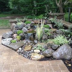 landscape design waterfalls water feature paver patio sitting wall with pillars, outdoor living, patio, ponds water features, Pondless Waterfall with Low Voltage Lighting and Rock Garden by Acorn Landscaping in Brighton NY Boulder Fountain with Waterfalls Outdoor Water Features, Water Features In The Garden, Small Water Features, Small Backyard Gardens, Backyard Garden Design, Courtyard Design, Large Backyard, Garden Pool, Shade Garden