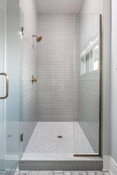 Behind a glass enclosure accented with a brass handle, a marble threshold leads to a walk-in shower fitted with gray glass subway surround tiles holding a brass shower kit above white marble grid floor tiles.