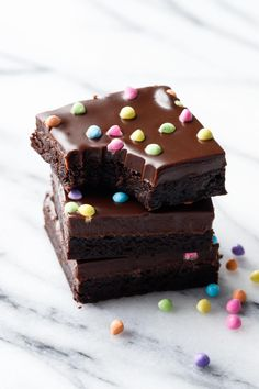 Ridiculously Fudgy Brownies made with just cocoa powder, topped with a simple chocolate ganache and rainbow sprinkles.