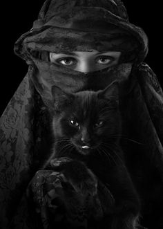 Veiled woman with black cat