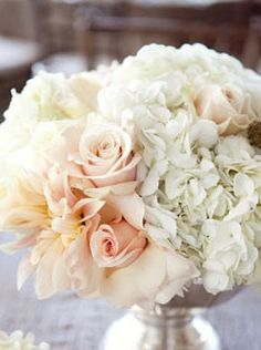 "The ceremony site and guest book table will feature arrangements of cream hydrangeas, blush pink ""Juliet"" garden roses, blush pink spray roses, ivory ""Patience"" garden roses, blush pink stock flowers, and grey dusty miller in large mercury glass vases."