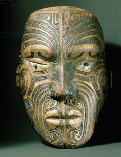 A carved wood Maori head with inlaid shell eyes