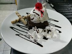 Black and White.  Browny served with ice cream, strawberries, almonds and peanuts.