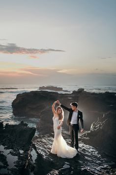 Gorgeous blue-toned skies with the sun in the distance and couple dressed in a white mermaid wedding gown and the simple black suit standing on cliffs // Following their dramatic ballroom wedding and gritty day-after-wedding photo shoot, Joshua and Cheryl are back to steam up our screens with a pre-wedding in Bali captured by Gustu of Maxtu Photography. Whether at a volcano, lake, waterfall, beach or cliffs, the connection Joshua and Cheryl share is palpable.