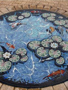 The Carterton Lily Pond Mosaic designed by Gary Drostle. Exterior floor mosaic koi pond in Carterton, Oxfordshire, United Kingdom. Pebble Mosaic, Mosaic Glass, Mosaic Tiles, Stained Glass, Glass Art, Tiling, Mosaic Floors, Flooring Tiles, Tile Art