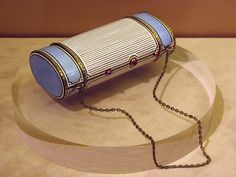 Faberge minaudiere made in gold with enamels and ruby details.