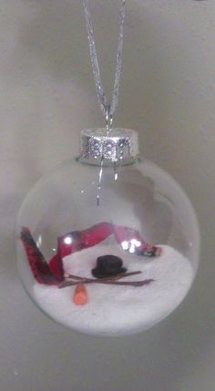 "DIY ""Australian Snowman"" Christmas Ornament -- All you need is a glass ornament, orange clay for the carrot nose, black clay for the top hat, fabric/ribbon cut into strips for the scarf (fray edges), 2 small twigs for arms, white craft sand & ribbon of your choice to hang the ornament."