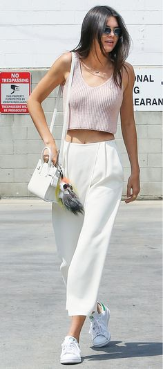 Kendall Jenner wears a blush pink knit crop top, white trousers, a white mini bag, Fendi keychain, aviator sunglasses, and Adidas sneakers
