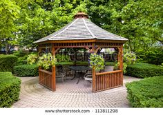 Gazebo in landscaped garden with interlocking stone patio - stock photo