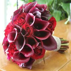 Red and Purple Bridal Hand-Tied Bouquet magnificent Bridal Hand-Tied Bouquet of Red Roses and Deep Plum Purple Mini Calla Lilies with Crystal Detail.