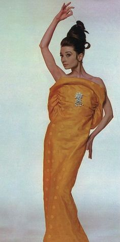 """The actress Audrey Hepburn photographed by Bert Stern at Vogue magazine's studio in New York City, New York (USA), specially for a fashion editorial called """"The Givenchy idea"""" (edition of April 15, 1963, unpublished photo), on March 15, 1963.Audrey was wearing:Evening gown: Givenchy (of silk shantung in a shade of vivid yellow covered with polka-dots, strapless, decorated in front by a brooch of big pearls and crystal beads, creating the false illusion of a flower, the model presents the…"""
