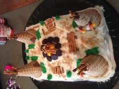 This is the cake Cooper and his fellow Boy Scouts designed for their banquet. The theme was Native American.  They used a regular sheet cake, brown and green icing, waffle cones, candy corns, pretzel sticks, Hershey Kisses and brown sugar.
