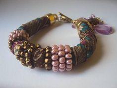 Pulseira de tecido estampado, anéis de miçangas coloridos e fechos e berloques dourados. Material resistente! R$ 19,90