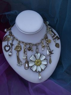 """Repurposed Vintage Jewelry Assemblage, titled """"The KEY to the GARDEN"""", featuring a repurposed earrings, a  flower pendant, beads,and charms. $95.00, via Etsy."""