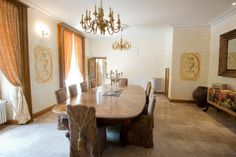 Grand dining room with large wooden dining table and chandelier in holiday rental château in Dordogne, France.