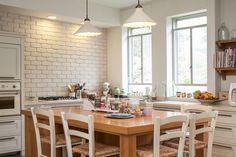 המטבח בסגנון כפרי, עם ארונות שדלתותיהן ממוסגרות, קיר לבנים צבוע לבן, ''אי'' לאחסון וארוחות יומיומיות ומעל הכיור שני חלונות גדולים, שפונים אל הפרגולה שבחוץ ( צילום: שירן כרמל  )