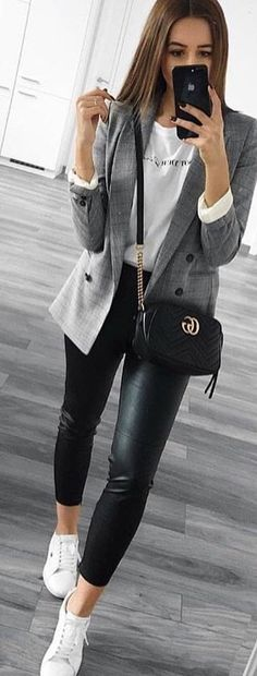#spring #outfits woman wearing gray blazer holding smartphone while standing. Pic by @vogue.story