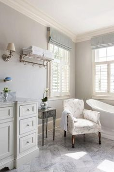An ivory and gray chair sits on marble herringbone floor tiles between a vintage freestanding tub and an antiqued mirror accent table lit by natural light from window dressed in gray linen roman shades.