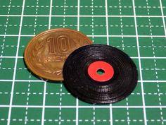 ミニチュアのレコード盤の作り方。 ミニチュアのレコード盤製作に関しては、下記のブログ記事が、とてもリアルで参考になります。 » 体験!ミニチュアLPレコード製作:別冊 梅屋千年堂:So-net blog 今回は、電動工具を使わない、アナログな方法で、レコード盤の作リ方を考えてみました。 まず、100円ショップで購入した、透明プラ板(厚さ0.2mm)を適当な大きさに切り出して、中央に0.5mmの穴を開けます。ちなみに、使用したドリル(0.5mm径)は、ダイソー製dです。 次に、サークルカッター(「コンパスカッター」とも言ったりしますね。)を準備します。(↓画像は、オルファ製のサークルカッター。)…