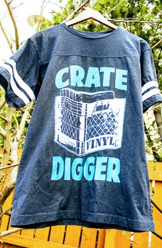 """DJ Football T-Shirt by THE GUNS OF BRIXTON. Cool navy blue color with two white stripes on both sleeves. The design from top to bottom consists of bold curved turquoise lettering that says, """"Crate"""" then a milk crate full of records, and finally the word """"Digger"""" also in bold turquoise. Do you like it? Click on any image to check out pricing, discount deals and shipping info. I'm an associate of Zazzle and I may earn a commission off the purchase of this product with no additional cost to…"""