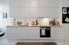 Interesting use of coloured benchtop to break up otherwise white on white colour scheme.