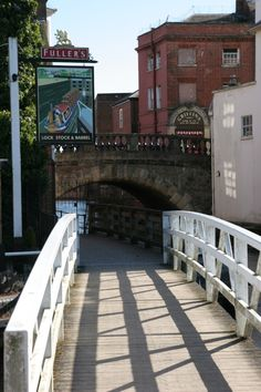 Wooden footbridge from Newbury's Lock Island to the town centre, leading to the footpath which passes the Lock Stock and Barrel pub. In the centre of the picture is the Town Water Bridge. This olde worlde bridge is probably the inspiration for Thomas Hardy's fictional Wessex town 'Kennetbridge' which scholars identify as being Newbury, Berkshire, England.