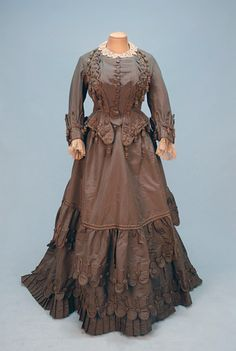 """PARIS LABEL SILK AFTERNOON GOWN, c. 1880. 3-piece mushroom silk faille elaborately decorated with scallops, braiding and tassels, semi-boned peplum bodice with self buttons and lace trim, trained skirt having deep hem ruffle above pleats with matching overskirt, petersham stamped """"Maison du Bon Marche Paris""""."""