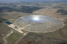 This is the Gemasolar Thermosolar Plant in Andalucía, Spain, which is a type of Concentrated Solar Power (CSP) plant. It works by reflecting sunlight off of heliostats (sun-tracking mirrors, basically) onto a tower where salts are heated. These heated salts are then used to create steam, which in turn runs a turbine that generates electricity. It is also capable of producing electricity day and night thanks to a salt storage system that can keep the turbine going for 16 hours. For more…