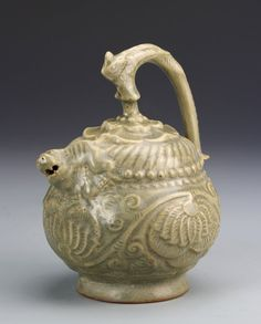 China, antique celadon glazed teapot, with a footed base, with two animal forms; one forming the spout and one forming the handle. Height 6 3/4 in.