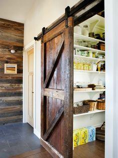 Eine sehr schöne dicke Holzbohle Schiebetür zeigt Essen hinter sich. Weiße Regale halten Ablagen und Körbe für eine besser organisierte Anordnung der Lebensmittel.