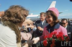 Jacqueline Kennedy carries her red roses (the only red ones she got in Texas) beams as she greets well wishers at Dallas' Love Field.