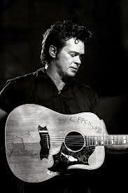 John Mellencamp and his famous 70's Gibson Dove. Apparently in an effort to emulate Pete Seeger's decorating his banjo with a social commentary, Mellencamp scratched a comment on the face of the Dove. Early on he covered it with a large band aid so as to not offend the Mothers in the crowd. He has used this guitar on most of his earlier albums and on tours. Recently he has used a Martin Mellencamp custom 00-18s acoustic guitar.