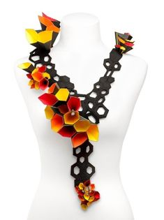 wowee!! :D ...The paper jewellery helps define the neckline. The brightly coloured flowers are very vibrant and iconic. The black base is very bold and it attracts the eye