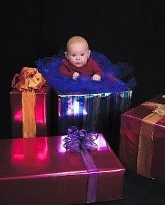 Wrap empty boxes for Christmas photo props. Baby is sitting on a bumpo seat hidden with tulle and tissue paper.