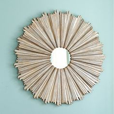 Suzanne Kasler loves sunburst mirrors, especially en masse. Large size is crafted of wood with high/low, staggered rays for dramatic visual texture.
