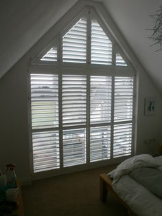 A tall gable end window with phoenix wood shutters.