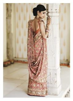 Bengali Style: Draped without pleats, it is wrapped around the waist and drawn back in a reverse pleat to the right side and then back. The pallu is taken, nicely pleated, over the left shoulder ensuring the border forms a straight line down the left to the floor. Once again pulled up from under the right arm, it corner is taken up to left shoulder, leaving a gorgeous drape at the back. Forms a very feminine and elegant drape.