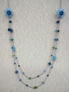 blues and greens. glass beads glass flowers at the collarbone