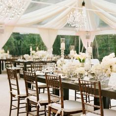 Clear tent. farm tables. white flowers. This.